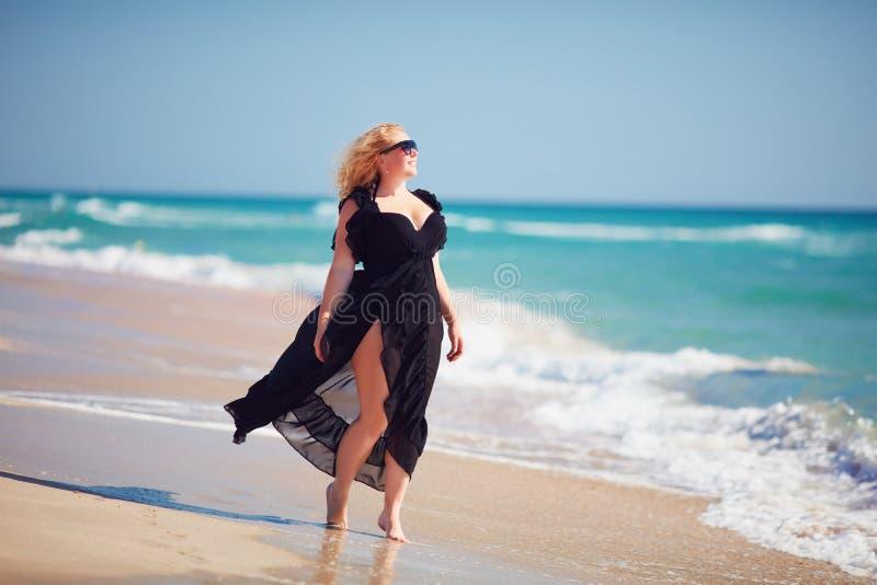 Het lichaamspositief, plus groottevrouw geniet de zomer van dag bij het strand stock fotografie