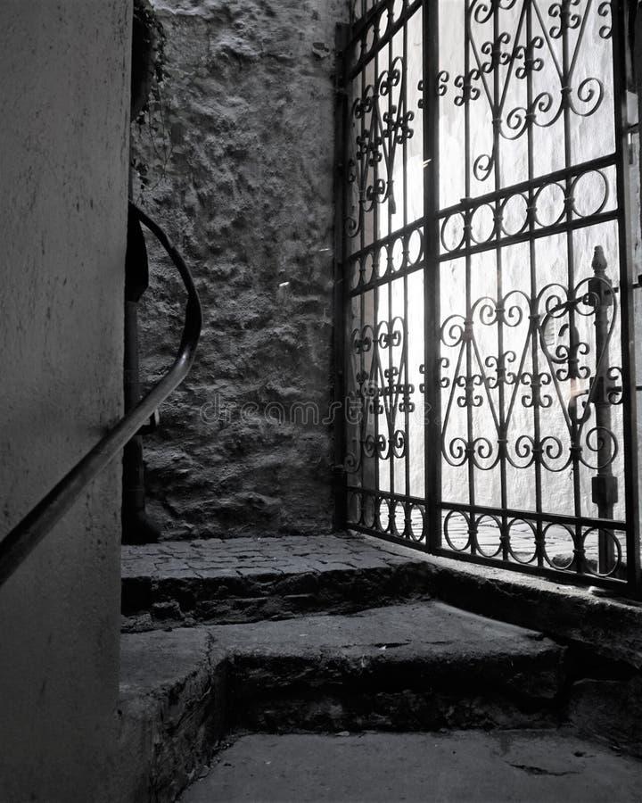Het licht glanst door gietijzer versperde deur in steenpassage stock afbeelding