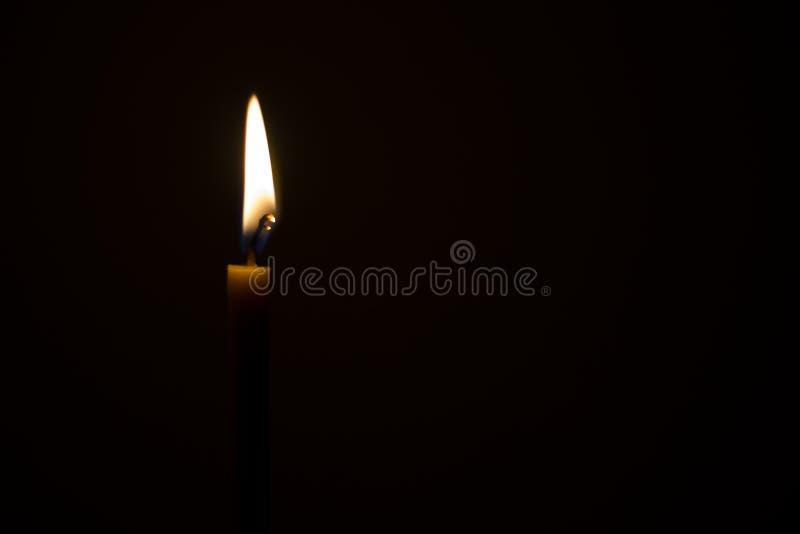 Het licht van de kaars in dark stock fotografie