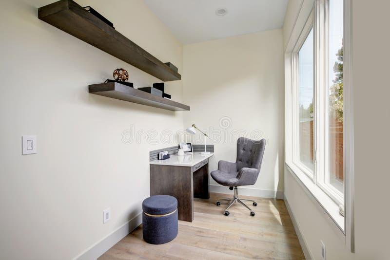 Het lichte kleine binnenland van het huisbureau met hoekbureau en een stoel royalty-vrije stock fotografie