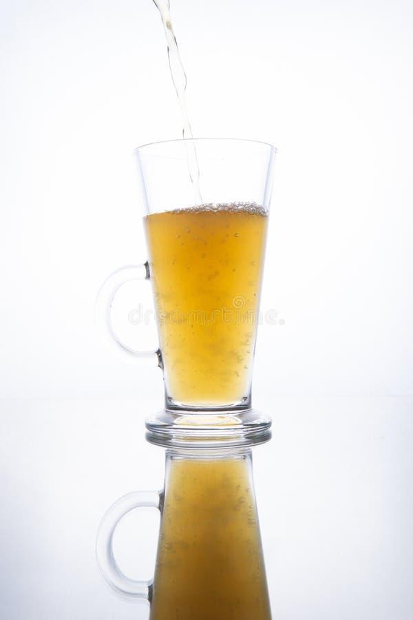 Het lichte ongefilterde bier goot in een stomende mok op een witte achtergrond met bezinning stock foto's