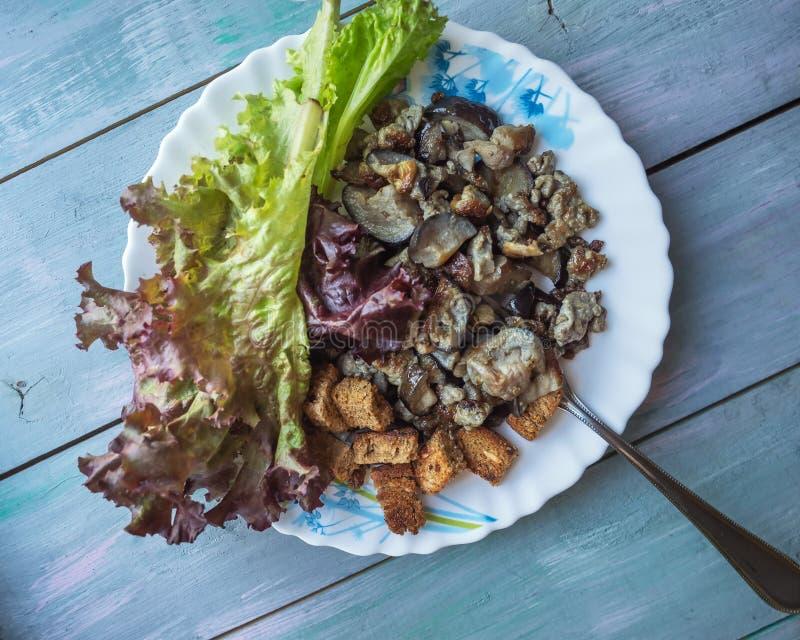 Het lichte ontbijt van gebraden aubergine, een blad van rode sla en de kleine croutons op een ronde plaat op een turkooise plank  royalty-vrije stock afbeelding