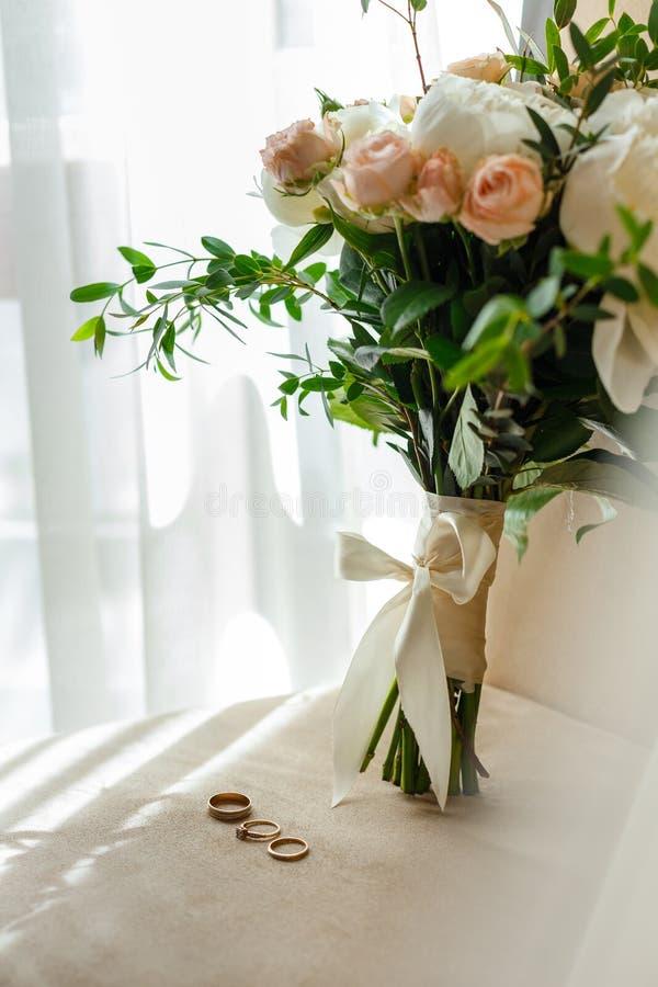 Het lichte tedere huwelijksboeket bevindt zich op de stoel samen met de huwelijksdetails van de bruid stock foto's