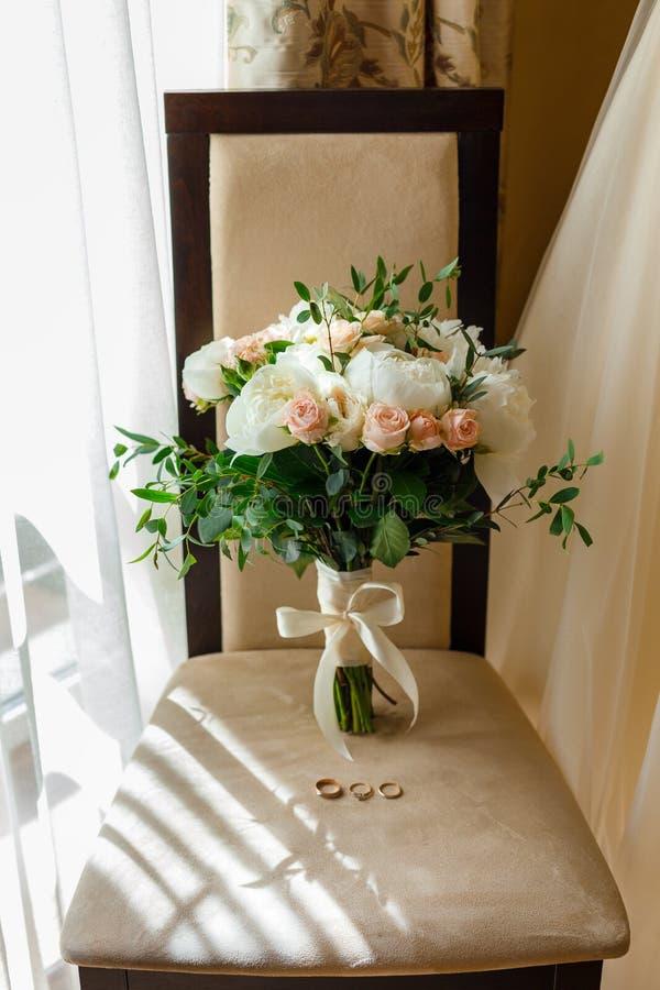 Het lichte tedere huwelijksboeket bevindt zich op de stoel samen met de huwelijksdetails van de bruid royalty-vrije stock afbeelding