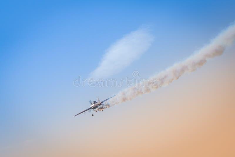 Het lichte vliegtuig vliegt onderaan het verlaten van achter zich een donkere rook als illustratie van neerstorting van privé str royalty-vrije stock foto's