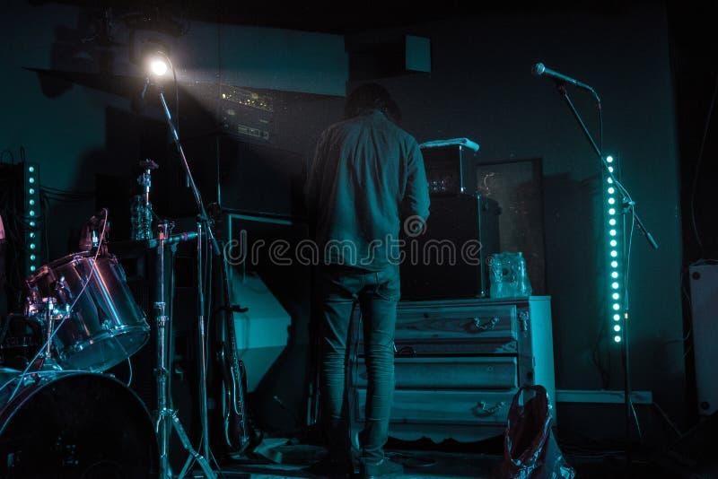 Het lid van band, musicus controleert het geluid vóór begin het spelen op stadium in neonlichten stock afbeeldingen