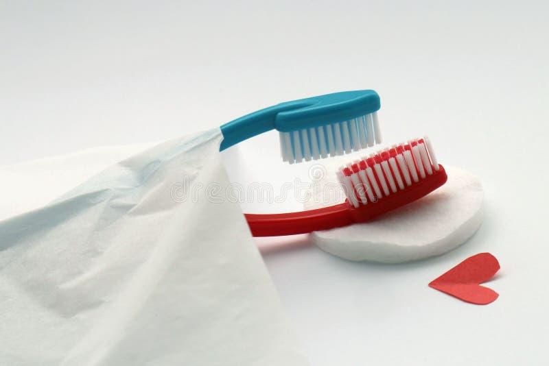 Het liefdeconcept tandenborstels, rode en blauwe totbrushes liggen in bed, ook de erotische missionary metafoor van positiebetrek royalty-vrije stock afbeeldingen