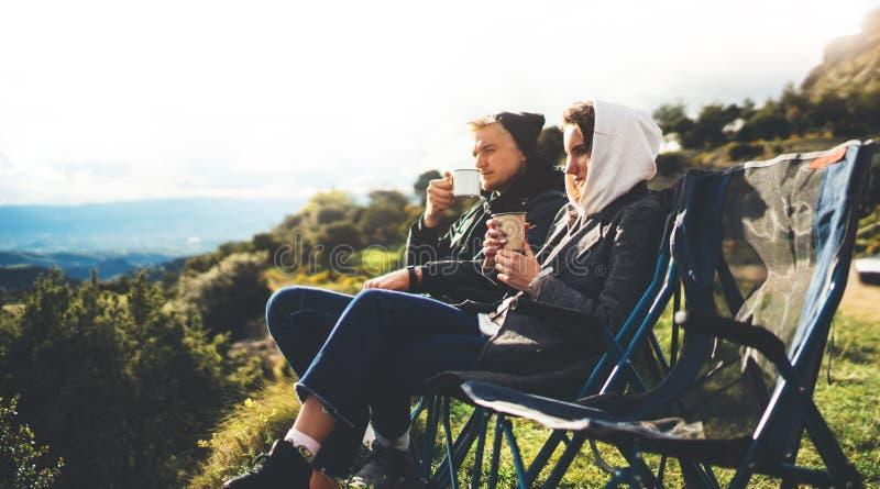 Het liefdepaar zit als het kamperen voorzitter bovenop de berg van de zongloed, drinken de reizigers thee op kop genieten van aar royalty-vrije stock afbeelding
