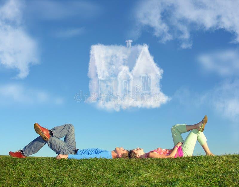 Het liggen paar op gras en de collage van het droomhuis stock afbeeldingen