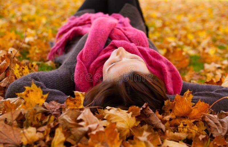 Het liggen van de herfst vrouw stock foto