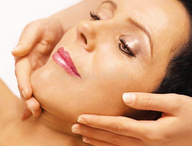 Het liggen van de vrouw, krijgt massage, reiki, op haar gezicht royalty-vrije stock afbeelding