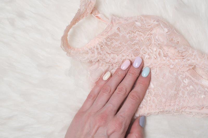 Het lijfje van het perzikkant in vrouwelijke hand Zachte manicure Close-up stock fotografie