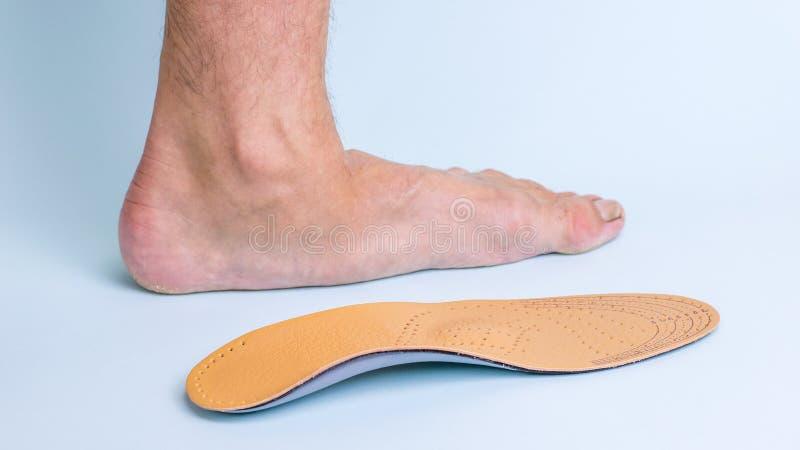 Het linkerbeen van een volwassen mannetje met tekens van voetziekte naast de orthopedische binnenzool Middelen voor de behandelin royalty-vrije stock afbeelding