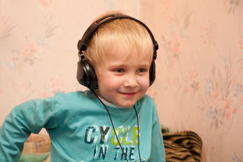 Het littening van de jongen aan muziek in hoofdtelefoons stock afbeeldingen