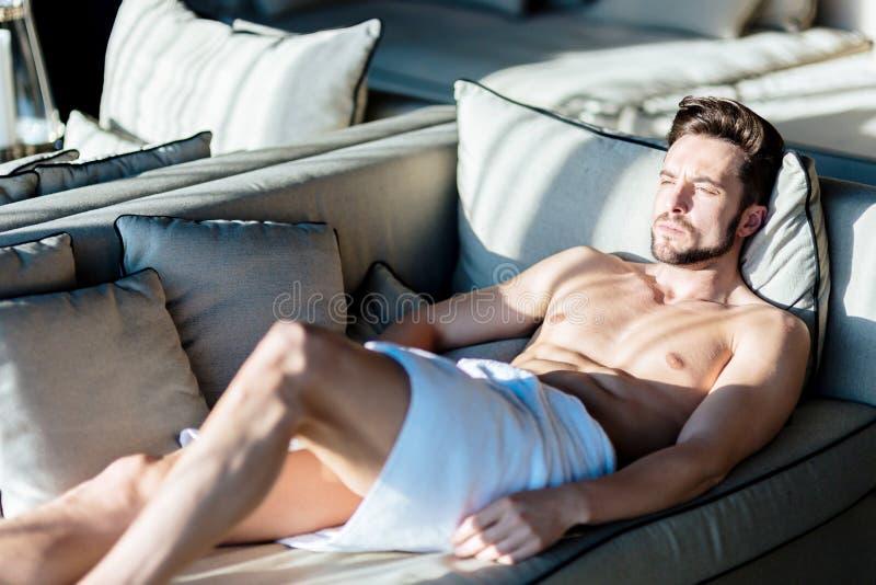 Het loensen het jonge, mooie mannelijke ontspannen op een laag in een hotel stock afbeeldingen