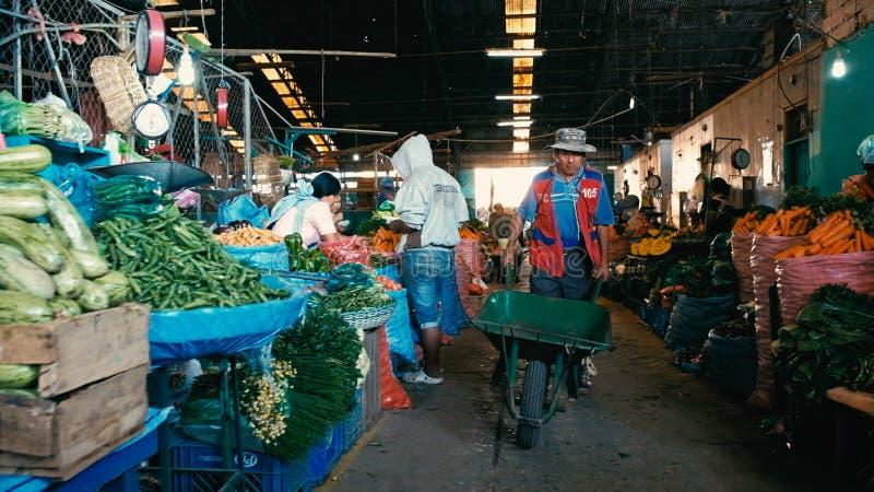 het lokale landbouwers verkopen hun opbrengst de stadsmarkt met een mens met een kruiwagen stock afbeelding