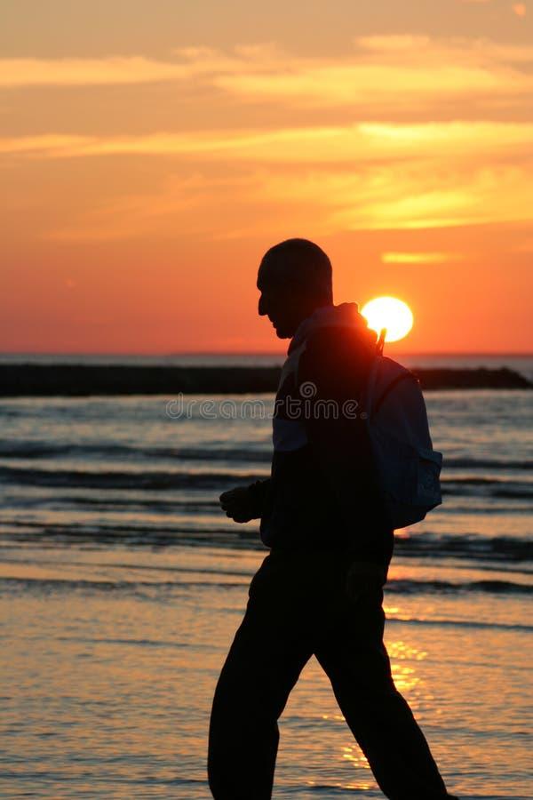 Het lopen bij zonsondergang stock foto's