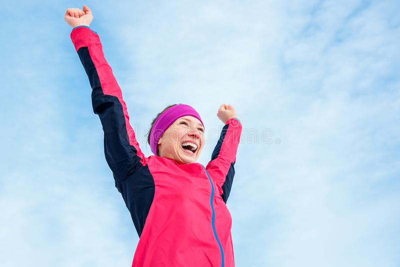 Het lopen en sportsucces Gelukkige vrouw het vieren overwinning en verhogingen zijn handen omhoog Vrouwelijke agent succesvol teg stock foto