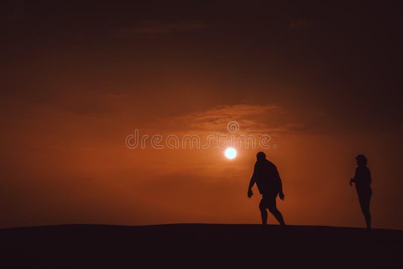 Het lopen op de zandduinen bij schemer stock foto