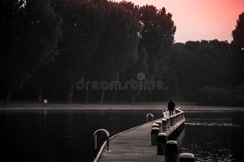 Het lopen op een brug aan de zonsopgang stock foto's