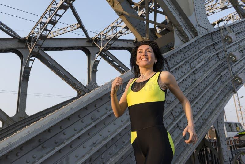 1 het lopen van het atletische witte meisje over de brug bij zonsondergang stock foto