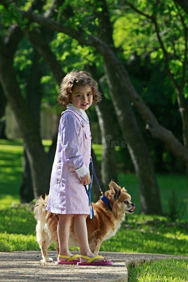 Het lopen van het meisje huisdierenhond stock foto