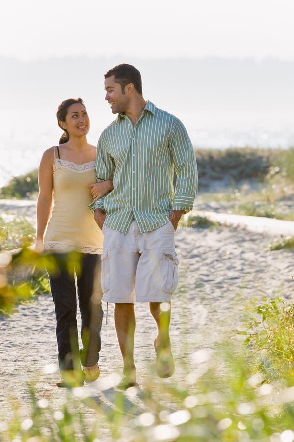 Het lopen van het paar holdingshanden bij strand royalty-vrije stock foto