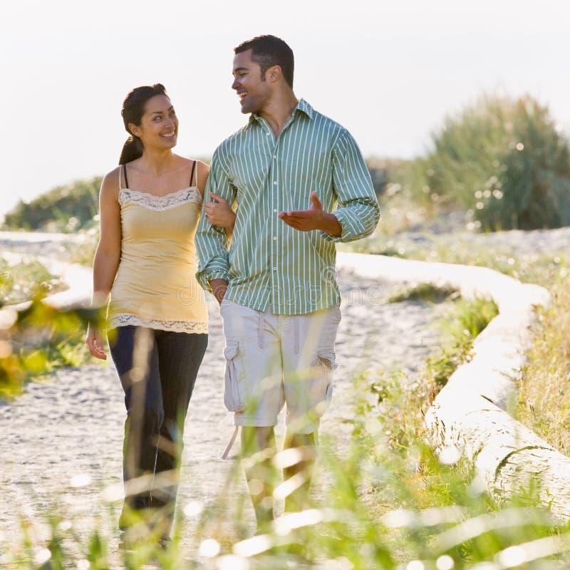 Het lopen van het paar holdingshanden bij strand royalty-vrije stock afbeelding