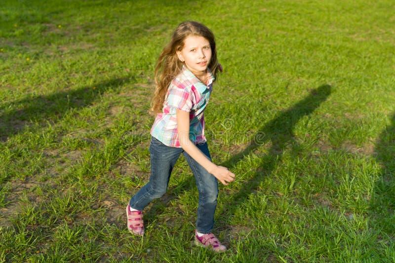 Het lopende meisje in het park, het kind heeft pret, speelt en loopt op het groene gazon royalty-vrije stock afbeeldingen