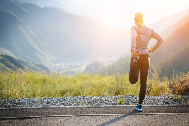 Het lopende uitrekken zich Atleet bij de bovenkant van de berg stock fotografie