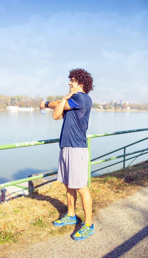 Het lopende uitrekken zich - mens die doend oefeningen in het park lopen royalty-vrije stock afbeelding