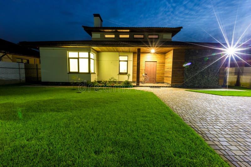 Het losgemaakte luxehuis bij nachtmening ziet uit van buiten op ingang royalty-vrije stock afbeeldingen