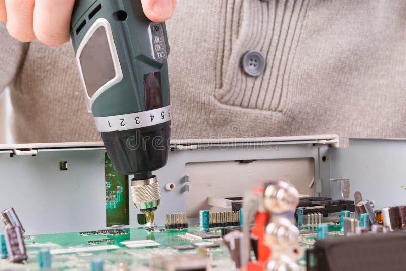 Het losschroeven van bout op PCB stock afbeeldingen