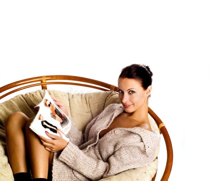 Het lounging van de vrouw op een laag met een tijdschrift stock foto