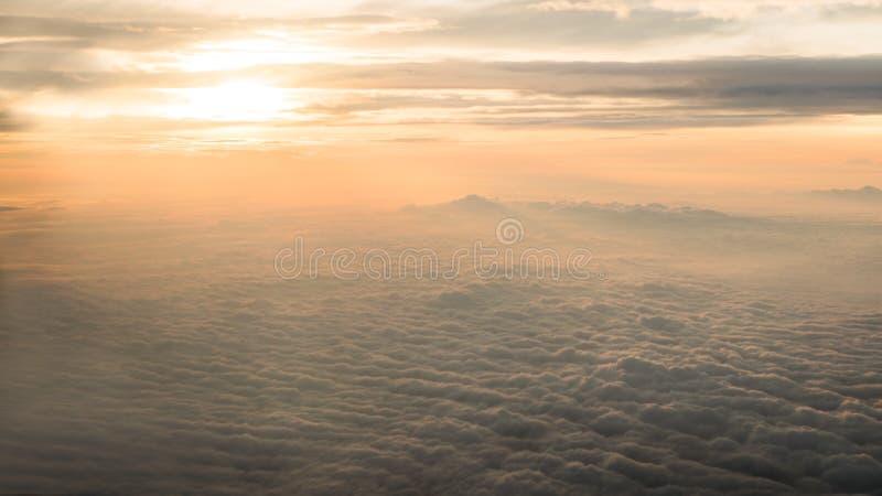 Het lucht reizen Het vliegen bij schemer of dageraad Vlieg door oranje wolk en zon stock foto