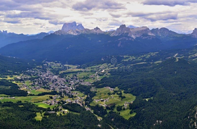 Het luchtbeeld van Cortinad Ampezzo - stad tussen groene bos en bergenpieken stock foto
