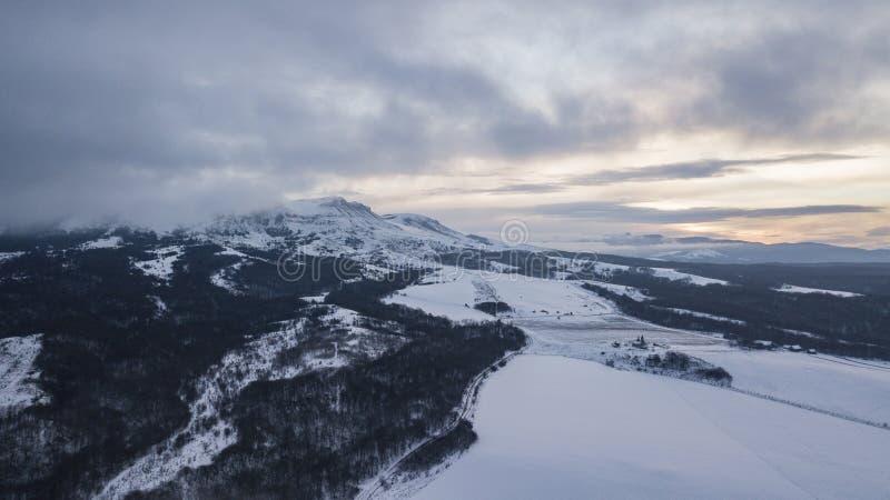 Het luchtlandschap van de bergwinter Fantastische ochtendwolken die door zonlicht gloeien royalty-vrije stock fotografie