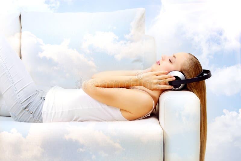 Het luisteren aan muziek in de wolken stock fotografie
