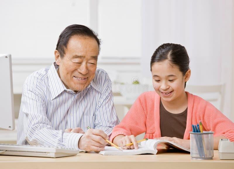 Het luisteren van het meisje aan grootvader verklaart thuiswerk stock fotografie