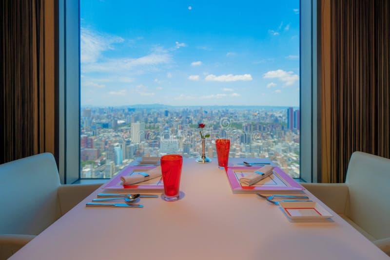 Het luxevaatwerk op lijst die in hotelrestaurant plaatsen met wolkenkrabbers en de gebouwen bekijken achtergrond in de Stad van T royalty-vrije stock foto