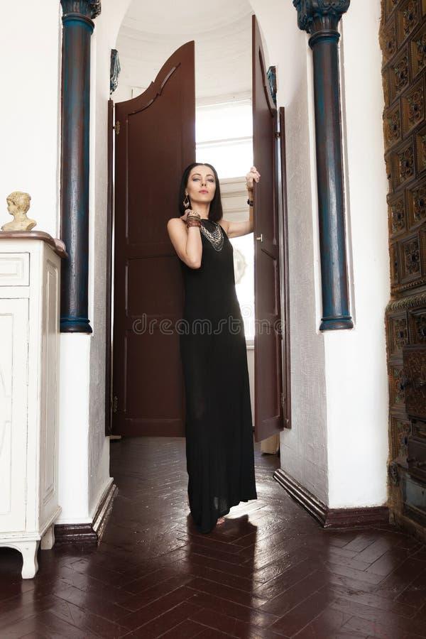 Het luxueuze donkerharige in een zwarte kleding en massieve gouden juwelen bevindt zich in de deuropening royalty-vrije stock fotografie
