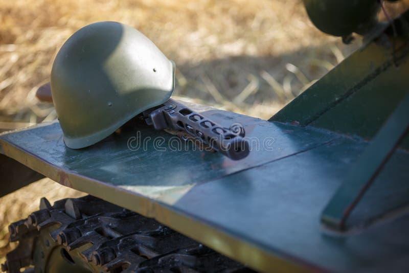 Het machinepistool van Shpagin, PPSh en de helm van Sovjetmilitair liggen op het pantser van de tank als illustratie aan de gebeu stock foto