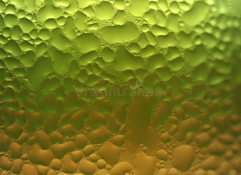 Het macroschot van water laat vallen textuur op het groene en oranje tweekleurige glas met selectieve nadruk stock foto's