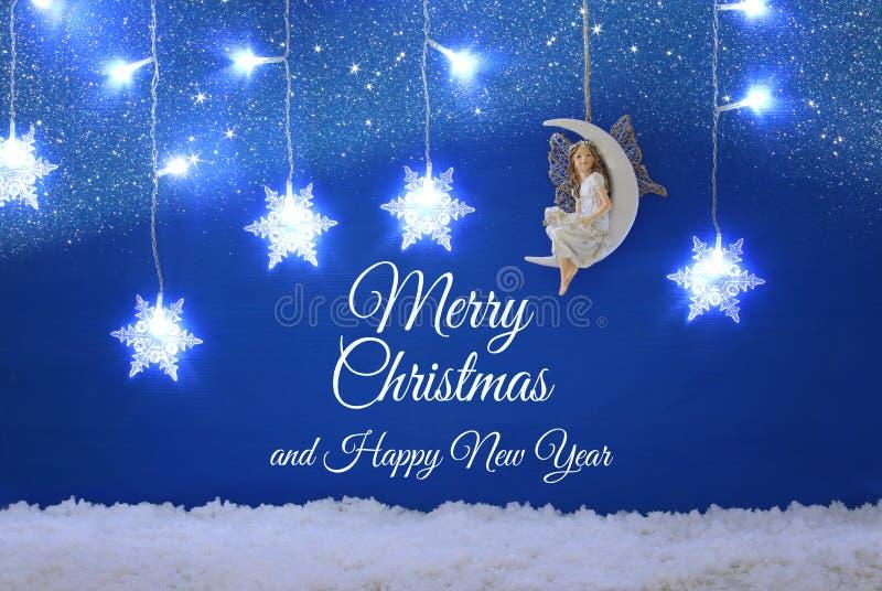 Het magische Kerstmisbeeld van weinig witte fee met schittert vleugels zittend op de maan over blauwe achtergrond en zilveren sne royalty-vrije stock afbeeldingen
