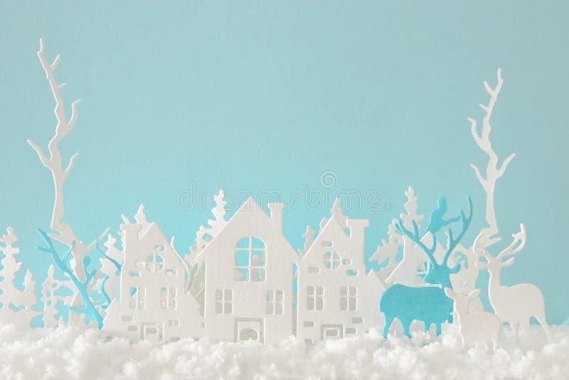 Het magische Kerstmisdocument sneed de winter achtergrondlandschap met huizen, bomen, herten en sneeuw voor pastelkleur blauwe ac royalty-vrije stock afbeeldingen