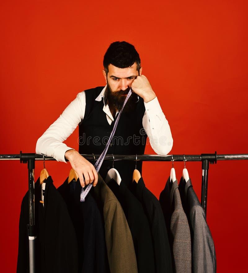 Het maken en gebrek aan het werkconcept De mens met baard door klerenrek, Ontwerper leunt op hand dichtbij douanejasjes royalty-vrije stock foto's