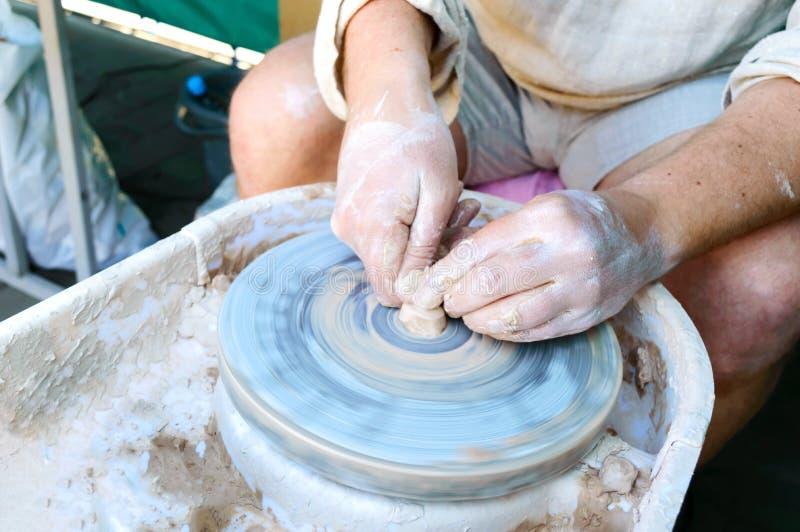 Het maken van aardewerk op een wiel van de pottenbakker Het close-up van de handenvakman, vormschotels Hoofdklasse royalty-vrije stock afbeelding