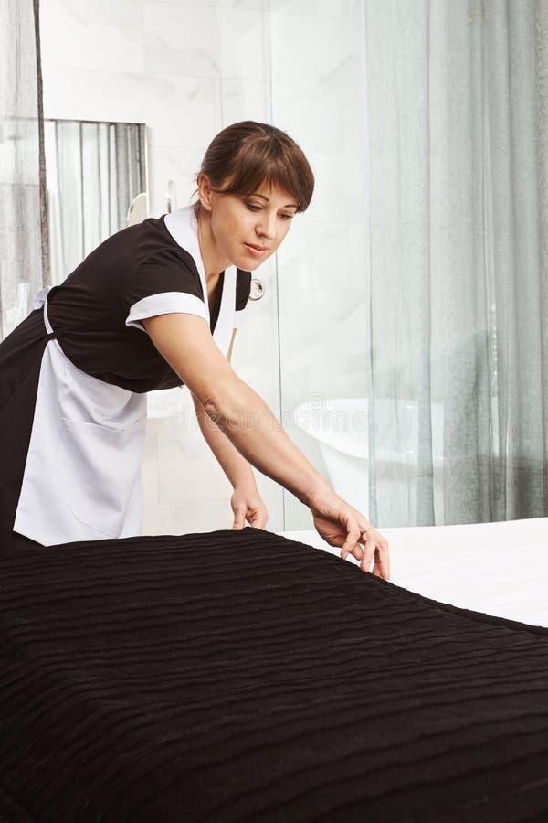 Het maken van bed is als art. Binnenschot die van meisje in eenvormig, deken op bed zetten terwijl het schoonmaken van hotelflat  stock foto