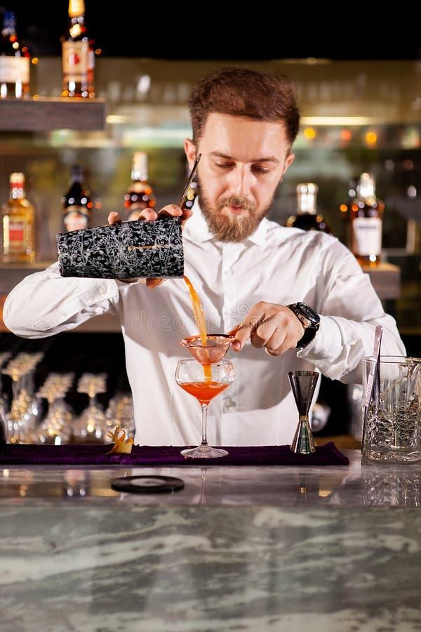 Het maken van cocktail bij de barteller stock foto