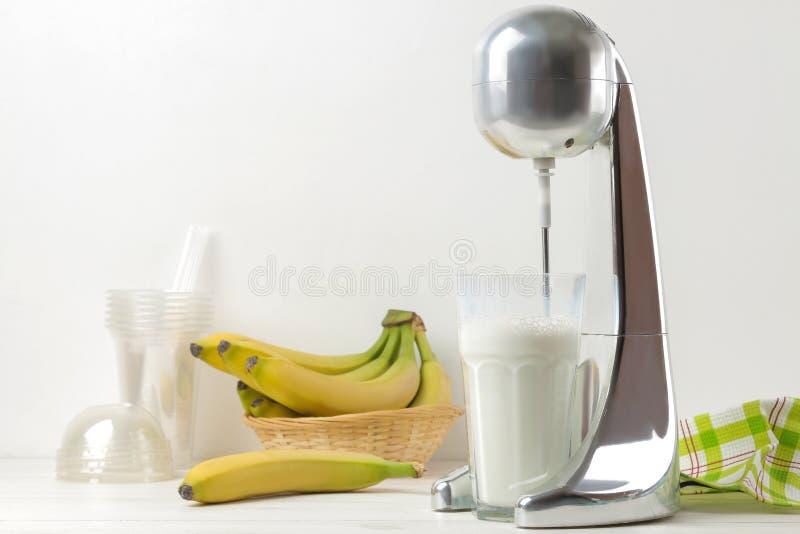 Het maken van een milkshake Mixer voor milkshake, beschikbare koppen en bananen op een lichte achtergrond Vrije ruimte stock fotografie
